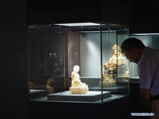 Visitors view porcelain statues displayed during an exhibition of Dehua porcelain held at Prince Kung's Mansion in Beijing, capital of China, Aug. 22, 2019. About 80 items of Dehua porcelain artworks made by artisans in southeast China's Fujian Province featuring Tibetan Buddhist statues in the Ming and Qing Dynasties (1368-1911) were on display during the ten-day exhibition, which kicked off here Thursday. Dehua porcelain is a type of white Chinese porcelain made in Dehua County of Fujian Province. Dehua is celebrated for its white porcelain, especially statues, such as those of Buddha. (Xinhua/Cui Bowen)