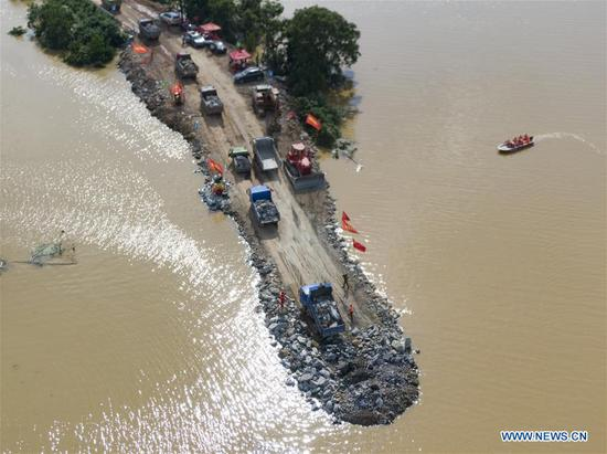 Aerial photo taken on July 12, 2020 shows the construction site of a breached dyke in Poyang Town of Poyang County, east China's Jiangxi Province. The embankment of a river in east China's Jiangxi Province was breached late Wednesday following continuous torrential rains, forcing over 9,000 residents to evacuate. (Xinhua/Zhang Haobo)