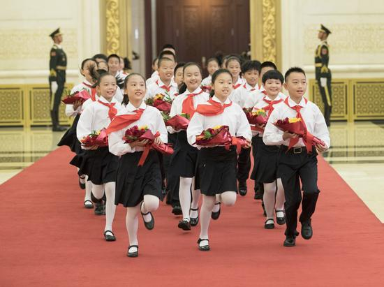 Children, who are members of Chinese Young Pioneers, present flowers to the awardees of national medals and honorary titles during the presentation ceremony in the Great Hall of the People in Beijing, capital of China, Sept. 29, 2019. (Xinhua/Wang Ye)