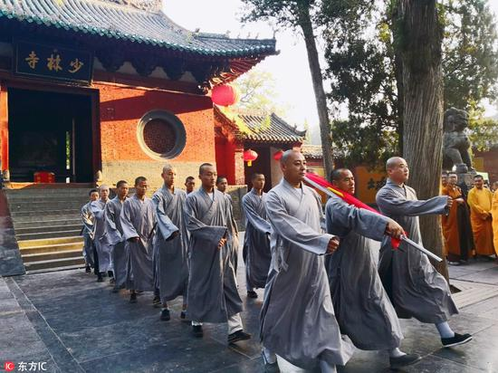 Holding the national flag, monks march toward the flag pole during a flag-raising ceremony in Shaolin temple on Songshan mountain in Central China's Henan province on Aug 27, 2018. The flag-raising ceremony, the first in the temple in more than 1,500 years, helps the religious circles and believers to enhance national and civic consciousness and consolidate the sense of the Chinese nation community, according to sources from the temple. Foreign believers were also present to witness the ceremony. [Photo/IC]