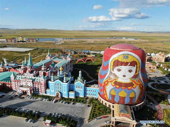 Photo taken with drone on Sept. 7, 2018 shows a square decorated with oversized Russian Matryoshka dolls in Manzhouli city of north China's Inner Mongolia Autonomous Region. Manzhouli, a border city with Russia, is benefiting from import and export trade between the two countries and witnessed a rapid economic and social development since China opened up to the world 40 years ago. (Xinhua/Zou Yu)