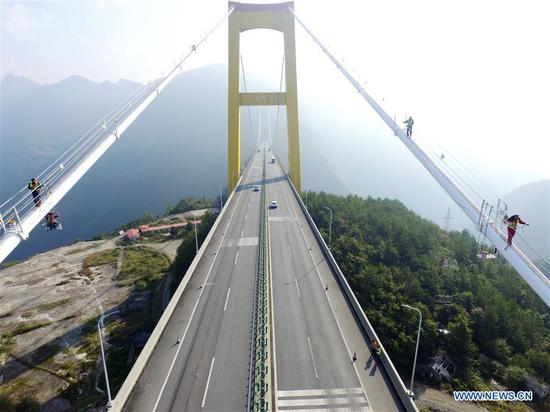 Staff members carry out cleaning and maintenance work on the main cables of the Sidu River Bridge in central China's Hubei Province, Oct. 10, 2018. The suspension bridge crosses the Sidu River valley near the boundaries of Yichang and Enshi in Hubei Province. The top point of the bridge is 650 meters above the bottom of the valley, a height comparable to a 200-storey skyscraper. (Xinhua/Zhu Wei)