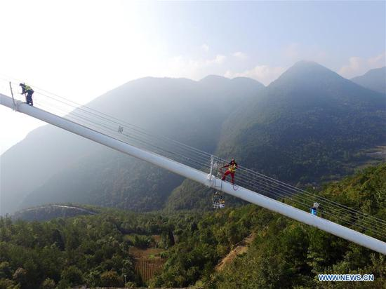 Staff members carry out cleaning and maintenance work on one of the main cables of the Sidu River Bridge in central China's Hubei Province, Oct. 10, 2018. The suspension bridge crosses the Sidu River valley near the boundaries of Yichang and Enshi in Hubei Province. The top point of the bridge is 650 meters above the bottom of the valley, a height comparable to a 200-storey skyscraper. (Xinhua/Zhu Wei)