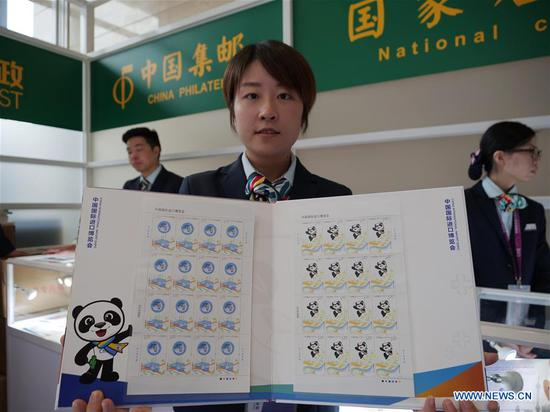 A staff member shows a set of stamps released to commemorate the China International Import Expo (CIIE) at the National Exhibition and Convention Center in Shanghai, east China, Nov. 5, 2018.(Xinhua/Wang Yiliang)