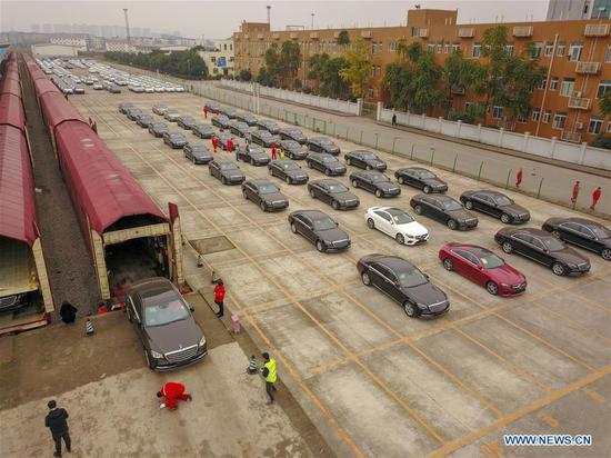 Aerial photo taken on Nov. 19, 2018 shows staff members unloading Mercedes-Benz cars from a carriage of a new China-Europe freight train carrying commercial vehicles, the first of its kind, in Chongqing, southwest China. The customs clearance process of those commercial vehicles was finished on Monday. The train, carrying 112 Mercedes-Benz cars, started its trip in Bremen, Germany on Oct. 29, and traveled 14,000 km across Germany, Poland, Lithuania, Belarus, Russia, and Kazakhstan, and arrived in Chongqing via the Horgos Port, Xinjiang Uygur Autonomous Region. The one-way trip took 16 days and 16 hours, reducing transportation time by more than two-thirds compared with by sea. Compared with shipping containers, train carriages are larger and less restricted by seasonal changes. (Xinhua/Liu Chan)