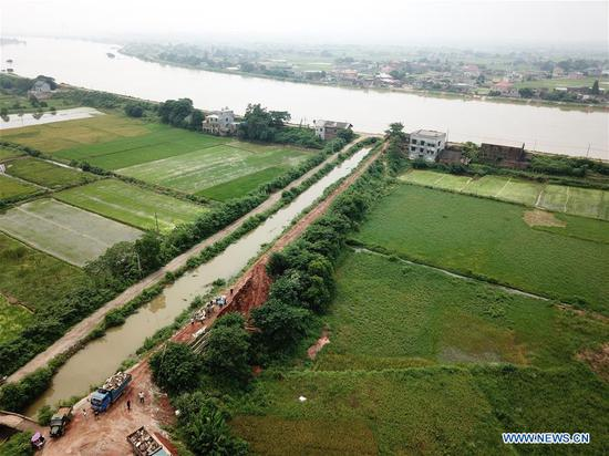 Aerial photo taken on July 10, 2019 shows the collapsed part of the dike of the Hongxing canal in Jiangshe village of Xiangtan City, central China's Hunan Province. Part of the dike of the Hongxing canal in Jiangshe village collapsed recently due to a series of heavy rainfall, which may cause a complete collapse and affect the surrounding villagers. The situation is under control after the joint efforts by locals to reinforce the dike. (Photo by Chen Zeguo/Xinhua)