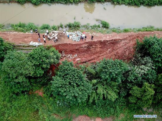 Aerial photo taken on July 10, 2019 shows people reinforcing the dike of the Hongxing canal in Jiangshe village of Xiangtan City, central China's Hunan Province. Part of the dike of the Hongxing canal in Jiangshe village collapsed recently due to a series of heavy rainfall, which may cause a complete collapse and affect the surrounding villagers. The situation is under control after the joint efforts by locals to reinforce the dike. (Photo by Chen Zeguo/Xinhua)