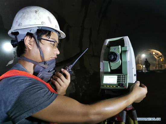 An engineer of China Railway No. 5 Engineering Group (CREC-5) works at the China-Laos railway Ban Konlouang Tunnel construction site in the Namor District of Oudomxay Province, Laos, Aug. 5, 2019. Rainy season in the Namor District of Oudomxay Province, some 400 km north of the Lao capital Vientiane, is relatively cool in late July, while at the Ban Konlouang Tunnel construction site, located inside mountains there, Chinese workers are sweating. The 9,020-meter Ban Konlouang Tunnel is the second longest tunnel along the China-Laos railway in northern Laos, which is constructed by China Railway No. 5 Engineering Group. (CREC-5/Handout via Xinhua)