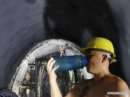 A worker of China Railway No. 5 Engineering Group (CREC-5) drinks water at the China-Laos railway Ban Konlouang Tunnel construction site in the Namor District of Oudomxay Province, Laos, July 30, 2019. Rainy season in the Namor District of Oudomxay Province, some 400 km north of the Lao capital Vientiane, is relatively cool in late July, while at the Ban Konlouang Tunnel construction site, located inside mountains there, Chinese workers are sweating. The 9,020-meter Ban Konlouang Tunnel is the second longest tunnel along the China-Laos railway in northern Laos, which is constructed by China Railway No. 5 Engineering Group. (CREC-5/Handout via Xinhua)