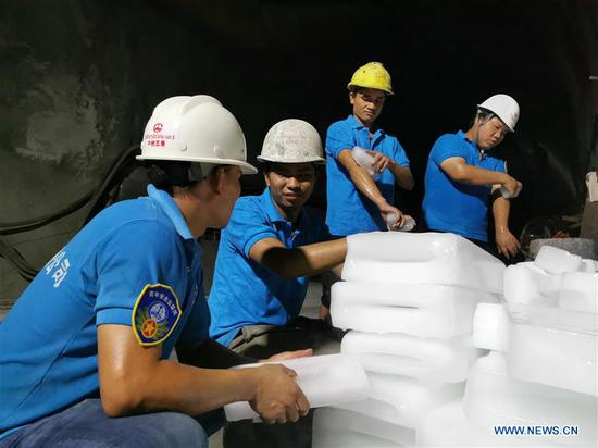 Workers of China Railway No. 5 Engineering Group (CREC-5) use ice blocks to cool off at the China-Laos railway Ban Konlouang Tunnel construction site in the Namor District of Oudomxay Province, Laos, Aug. 1, 2019. Rainy season in the Namor District of Oudomxay Province, some 400 km north of the Lao capital Vientiane, is relatively cool in late July, while at the Ban Konlouang Tunnel construction site, located inside mountains there, Chinese workers are sweating. The 9,020-meter Ban Konlouang Tunnel is the second longest tunnel along the China-Laos railway in northern Laos, which is constructed by China Railway No. 5 Engineering Group. (CREC-5/Handout via Xinhua)