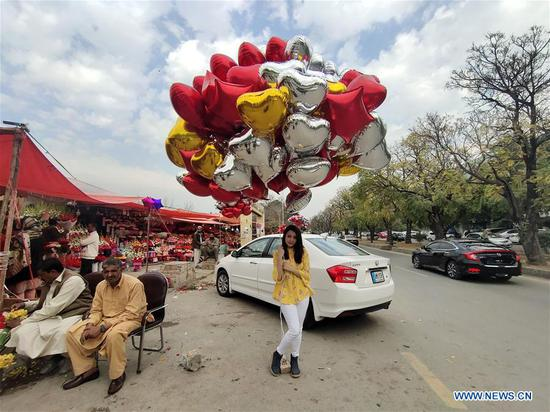A girl poses for a photo with heart-shaped balloons before Valentine's Day in Islamabad, Pakistan, Feb. 13, 2020. (Xinhua/Ahmad Kamal)