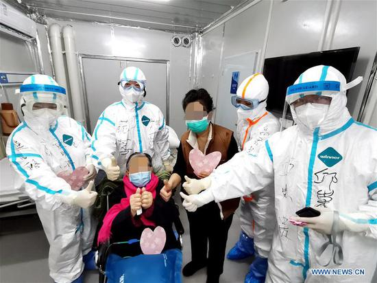 Photo taken with a mobile phone shows a 98-year-old woman patient (in a wheelchair) and her daughter (3rd R) taking a group photo with medical workers before leaving the Leishenshan hospital in Wuhan, central China's Hubei Province, March 1, 2020. A 98-year-old woman patient of the novel coronavirus disease (COVID-19), so far the oldest critical patient cured in China, has been discharged from a makeshift hospital in Wuhan, capital of central China's Hubei Province, Sunday after recovery.(Photo by Gao Xiang/Xinhua)