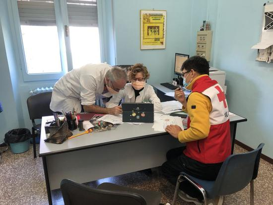 A member of the Chinese medical team talks with medics working at the Pavia hospital in Pavia, Italy, March 21, 2020. (Xinhua)