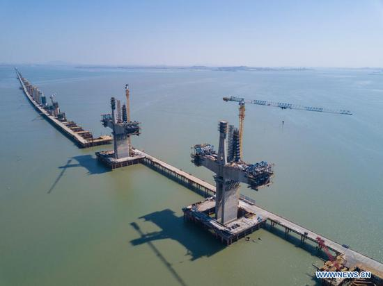 Aerial photo taken on Feb. 15, 2021 shows the construction site of Meizhou Bay cross-sea bridge of the Fuzhou-Xiamen high-speed railway in southeast China's Fujian Province. Some 500 laborers still work at the construction site of the bridge during the Chinese Lunar New Year. The 14.7-km-long bridge is part of the province's Fuzhou-Xiamen high-speed railway, the first cross-sea high-speed railway in China, which is expected to be put into operation in 2022. (Xinhua/Song Weiwei)