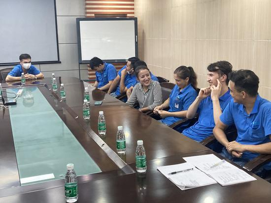 Nilufer Gheyret (4th R) talks with Xinjiang migrant workers of the Uygur ethnic group during an interview at a company in south China's Guangdong Province, Sept. 17, 2020. (Photo by Chen Ning/Xinhua)