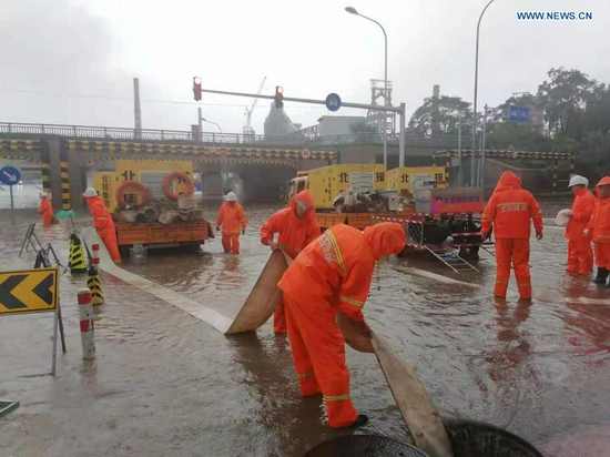 Staff members from Beijing Drainage Group drain water from a waterlogged street as rainstorms hit Shijingshan District in Beijing, capital of China, July 18, 2021. The Beijing Meteorological Observatory on Sunday morning issued an orange warning for rainstorms after the accumulated rainfall in some areas of the capital had exceeded 150 mm. (Xinhua)