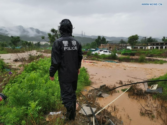 A police officer checks a road ruined by rainstorm-triggered flood in Mentougou District in Beijing, capital of China, July 18, 2021. The Beijing Meteorological Observatory on Sunday morning issued an orange warning for rainstorms after the accumulated rainfall in some areas of the capital had exceeded 150 mm. (Xinhua)