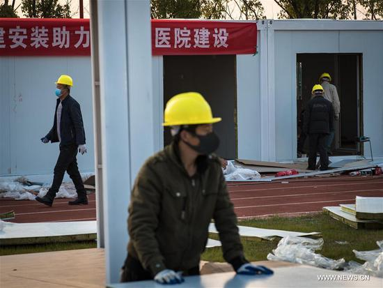 People from China Construction Third Engineering Bureau Co., Ltd. work at the construction site of Leishenshan (Thunder God Mountain) Hospital in Wuhan, central China's Hubei Province, Jan. 30, 2020. Wuhan is building two hospitals to treat pneumonia patients infected with the novel coronavirus. As of Thursday noon, about 40 percent of the Leishenshan Hospital has been completed, and it is expected to be put into use on Feb. 5. (Xinhua/Xiao Yijiu)