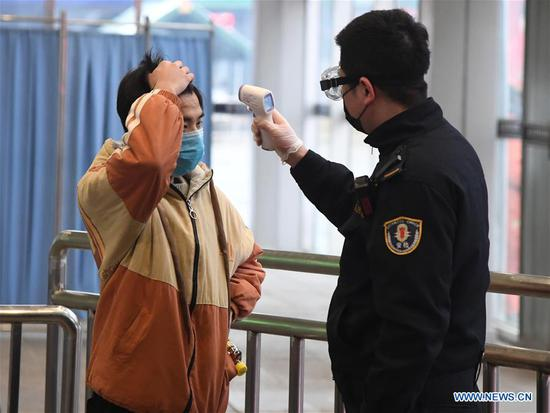 A staff member measures temperature for a passenger at Beijing West Railway Station in Beijing, capital of China, Feb. 2, 2020. Chinese authorities have tightened measures to battle the novel coronavirus epidemic as a growing number of people hit the road and return to work after the Spring Festival holiday. (Photo by Ren Chao/Xinhua)