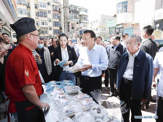 Chinese Premier Li Keqiang, also a member of the Standing Committee of the Political Bureau of the Communist Party of China Central Committee, talks with a stallholder in front of a grocery store on the Dongyuan Street in Yantai, east China's Shandong Province, June 1, 2020. Li made an inspection tour of Shandong Province from Monday to Tuesday. (Xinhua/Pang Xinglei)