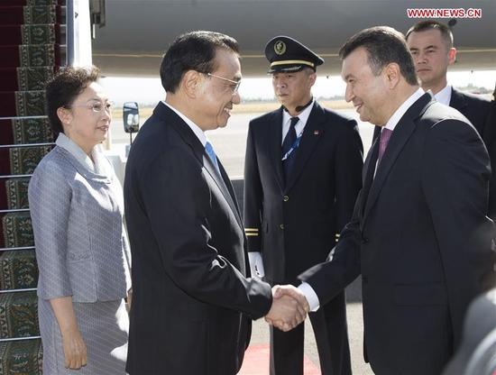 Chinese Premier Li Keqiang is welcomed by Tajik Prime Minister Kokhir Rasulzoda upon his arrival at the Dushanbe international airport in Dushanbe, Tajikistan, Oct. 11, 2018. Li Keqiang arrived here on Thursday for an annual meeting of heads of government of the Shanghai Cooperation Organization member states and an official visit to Tajikistan. (Xinhua/Huang Jingwen)