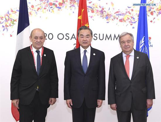 Chinese State Councilor and Foreign Minister Wang Yi (C), French Foreign Minister Jean-Yves Le Drian (L) and UN Secretary-General Antonio Guterres pose for a group photo before a trilateral meeting held on the sidelines of a summit of the Group of 20 major economies, in Osaka, Japan, June 29, 2019. Wang Yi called upon all parties to honor their commitments and take concrete actions in tackling climate change at the meeting on Saturday. (Xinhua/Yan Yan)
