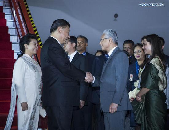 Chinese President Xi Jinping (2nd L) and his wife Peng Liyuan (1st L) are greeted by Mauritian Prime Minister Pravind Jugnauth and his wife Kobita Ramdanee at the airport in Port Louis July 27, 2018. Xi arrived in Port Louis on Friday for a friendly visit to Mauritius. (Xinhua/Li Xueren)