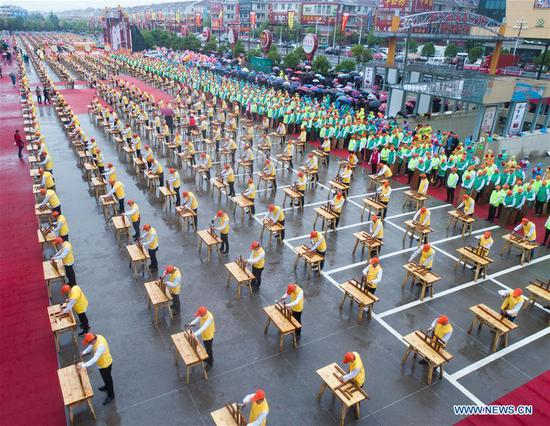 Aerial photo taken on April 11, 2019 shows craftsmen demonstrating skills of making wooden crafts at Huayuan Village of Nanma Town in Dongyang, east China's Zhejiang Province. Huayuan is a renowned wooden crafts and mahogany furniture wholesale market in China, as well as a scenic area in the region. (Xinhua/Xu Yu)
