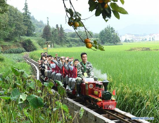 Pupils taking a mini train enjoy the harvest scenery of paddy fileds during an event celebrating the Chinese Farmers' Harvest Festival in Datong Town of Jiande City, east China's Zhejiang Province, Sept. 22, 2020. (Xinhua/Weng Xinyang)