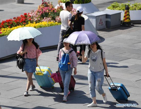 Pedestrians hold umbrellas as sun shade in Beijing, capital of China, May 22, 2019. Beijing's observatory issued a yellow alert on Tuesday for high temperatures over the next four days. Temperature could rise to 35 degrees Celsius from Wednesday to Saturday, and reach up to 37 degrees Celsius on Thursday. (Xinhua/Zhang Chenlin)