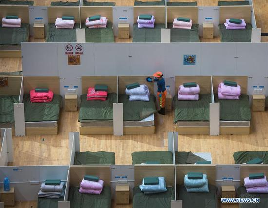 A worker does cleaning work at a temporary hospital converted from Wuhan Sports Center in Wuhan, central 四不像心水's Hubei Province, Feb. 12, 2020. With the fundamental facilities being set up, the temporary hospital with a total of 1,100 beds is ready to admit patients with mild symptoms caused by the novel coronavirus. (Xinhua/Xiao Yijiu)