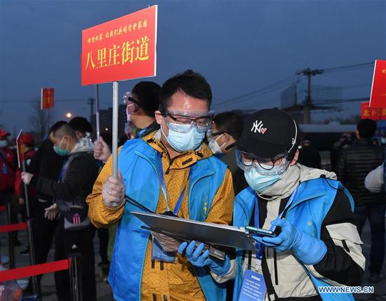 Staff members check the information of people returning from Hubei at a gathering point in Haidian District in Beijing, capital of China, March 25, 2020. The first batch of over 800 people stranded in virus-hit Hubei Province has arrived in Beijing Wednesday afternoon after Hubei lifted outbound travel restrictions in all areas except the capital city Wuhan starting from Wednesday. (Xinhua/Ren Chao)