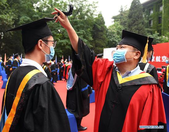 Sun Cong (R), president of the Chinese Aeronautical Establishment, also an alumnus of Beihang University, turns the tassel for a graduate at the commencement ceremony at Beihang University in Beijing, capital of China, June 29, 2020. Beihang University held a commencement ceremony for the Class of 2020 (Bachelor's Degrees) on Monday. In order to reduce the risk of infection of COVID-19, only a minority of graduates attended the ceremony on site with the others attending online. (Xinhua/Ren Chao)