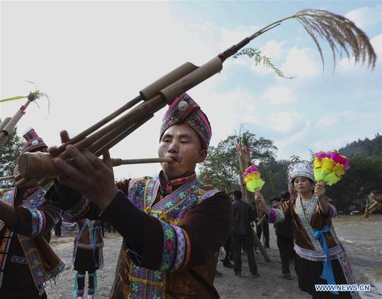 People of Miao ethnic group play lusheng, a musical instrument made of multiple bamboo pipes, during a harvest festival in Dongtou Village, Rongshui Miao Autonomous County, south China's Guangxi Zhuang Autonomous Region, Oct. 26, 2018. Local people celebrated harvest Friday through various activities like fish feast, singing and playing lusheng. (Xinhua/Lan Hongguang)
