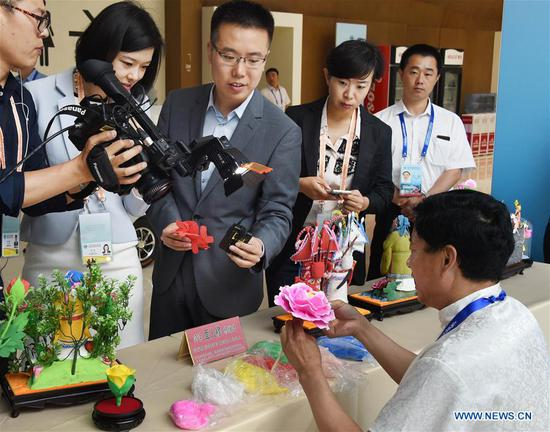 Craftsman Mu Xujian shows dough sculpture making to journalists at the media center for the 18th Shanghai Cooperation Organization (SCO) Summit in Qingdao, east China's Shandong Province, June 6, 2018. (Xinhua/Guo Xulei)