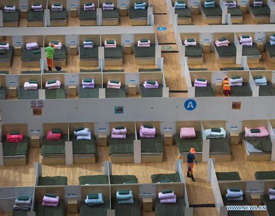 Workers clean a temporary hospital converted from Wuhan Sports Center in Wuhan, central China's Hubei Province, Feb. 12, 2020. With the fundamental facilities being set up, the temporary hospital with a total of 1,100 beds is ready to admit patients with mild symptoms caused by the novel coronavirus. (Xinhua/Xiao Yijiu)