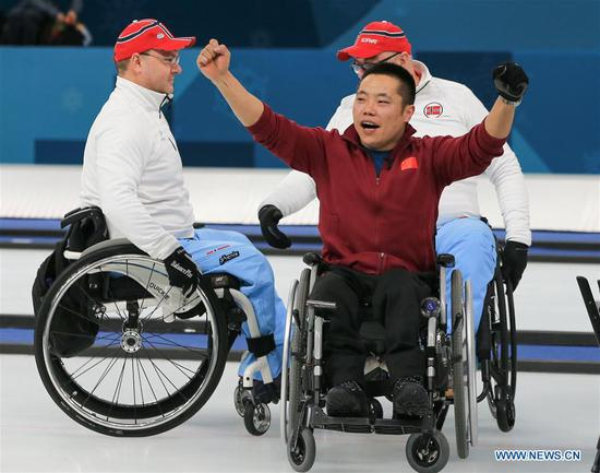 China's Liu Wei (front) celebrates after winning the wheelchair curling final against Norway at the 2018 PyeongChang Winter Paralympic Games at Gangneung, South Korea, March 17, 2018. China beat Norway in the final 6-5 to claim the title of the event, which is also China's first-ever Winter Paralympic medal with gold. (Xinhua/Wang Jingqiang)