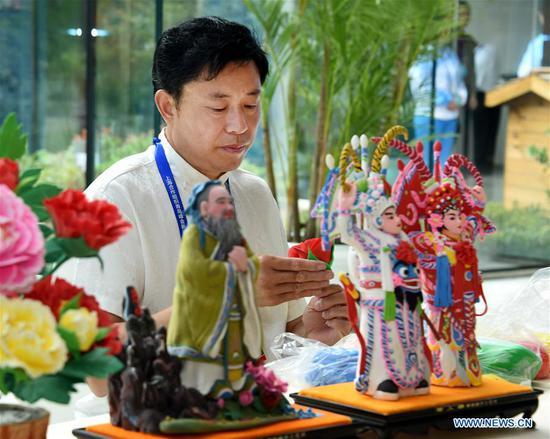 Craftsman Mu Xujian makes dough sculptures at the media center for the 18th Shanghai Cooperation Organization (SCO) Summit in Qingdao, east China's Shandong Province, June 6, 2018. (Xinhua/Li Ziheng)