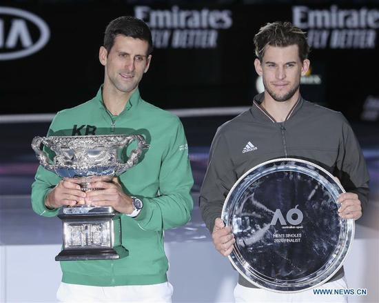 Novak Djokovic (L) of Serbia and Dominic Thiem of Austria pose with the trophy during the awarding ceremony after the men's singles final at 2020 Australian Open in Melbourne, Australia on Feb. 2, 2020. (Xinhua/Wang Jingqiang)
