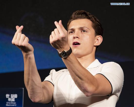 Actor Tom Holland greets fans during a press conference of the film
