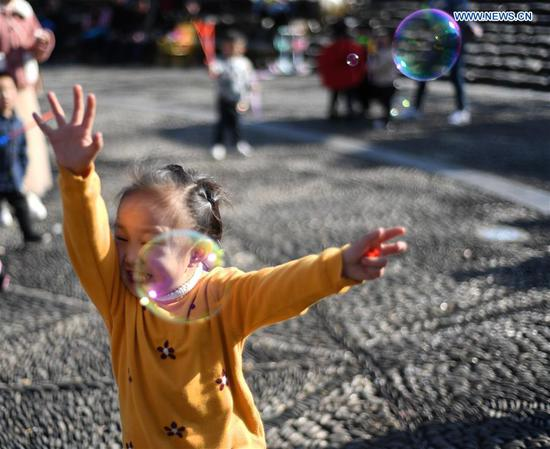 A child chases bubbles in Leishan County of Qiandongnan Miao and Dong Autonomous Prefecture in southwest China's Guizhou Province, Feb. 6, 2019. (Xinhua/Cai Xingwen)