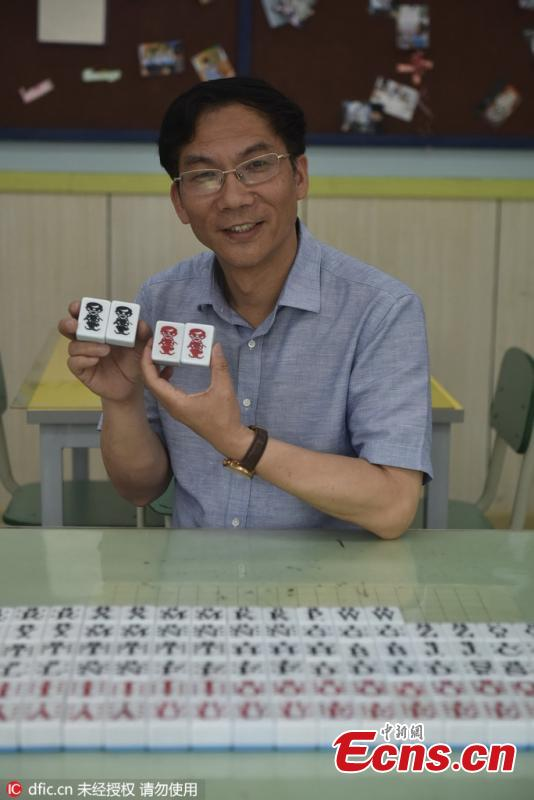 A teacher shows mahjong tiles that have been modified to help with learning English at Jitou Middle School in Chengdu City, the capital of Southwest China's Sichuan Province, May 31, 2016. (Photo/IC)