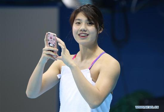 Chinese swimming athlete Zhang Yufei takes photos during a training session at the Olympic Aquatic Stadium in Rio de Janeiro, Brazil, July 31, 2016. Members of Chinese national swimming team arrived in Rio de Janeiro and began their first adaptive training on Sunday. (Xinhua/Ding Xu)
