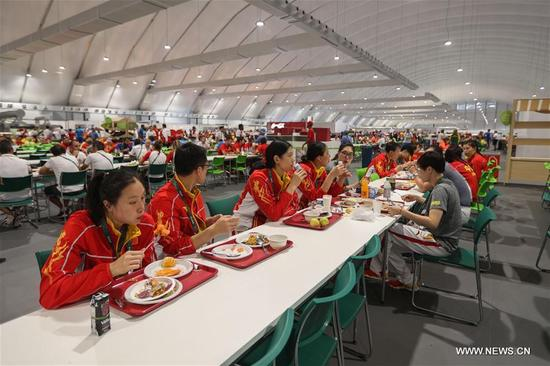 Members of the delegation of China are seen in the canteen at the Olympic village in Rio de Janeiro, Brazil, on Aug. 2, 2016. With 31 buildings and 3,604 apartments, the village will host more than 17,000 athletes and officials during its peak times. Built in the neighbourhood of Recreio dos Bandeirantes in the west of Rio, it is close to Barra Olympic Park, the main venue cluster. (Xinhua/Zheng Huansong)