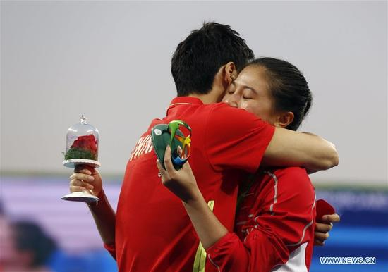 Silver medallist China's He Zi(R), receives a marriage proposal from Olympic diver Qin Kai of China after the awarding ceremony for the Women's diving 3m Springboard Final at the Rio 2016 Olympic Games at the Maria Lenk Aquatics Stadium in Rio de Janeiro, Brazil on Aug. 14, 2016. (Xinhua/Ding Xu)