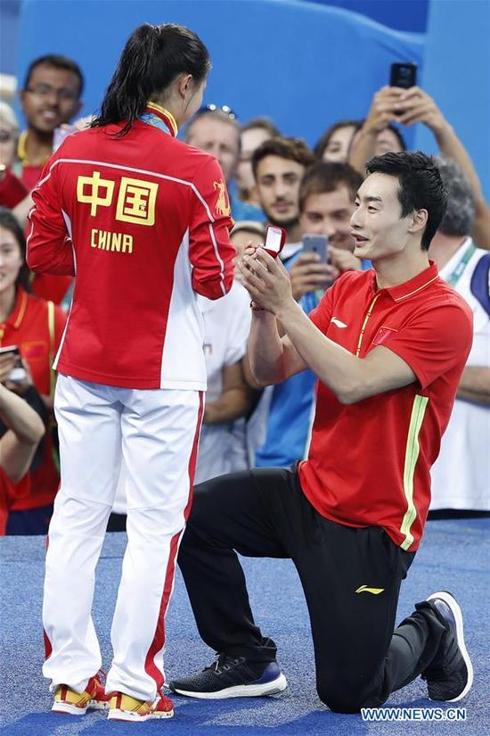 Silver medallist China's He Zi (L), receives a marriage proposal from Olympic diver Qin Kai of China after the awarding ceremony for the Women's diving 3m Springboard Final at the Rio 2016 Olympic Games at the Maria Lenk Aquatics Stadium in Rio de Janeiro, Brazil on Aug. 14, 2016. (Xinhua/Fei Maohua)