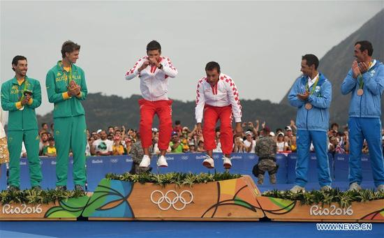 Gold medalist Croatia's Sime Fantela (3rd, L) and Igor Marenic(4th, L) jump onto the podium during the awarding ceremony for 470 men medal race of Sailing at the 2016 Rio Olympic Games in Rio de Janeiro, Brazil, on Aug. 18, 2016. (Xinhua/Li Ga)