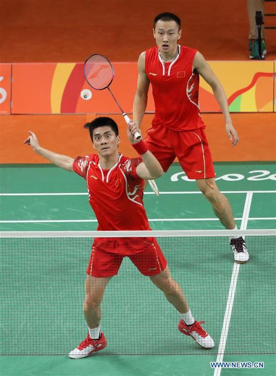 China's Zhang Nan (behind) and Fu Haifeng compete during the men's doubles badminton gold medal match against Malaysia's Goh V Shem and Tan Wee Kiong at the 2016 Rio Olympic Games in Rio de Janeiro, Brazil, on Aug. 19, 2016. Zhang Nan and Fu Haifeng won the gold medal. (Xinhua/Meng Yongmin)