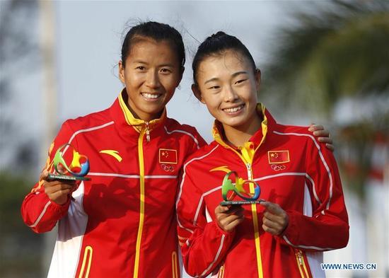China's Liu Hong (L) and Lu Xiuzhi celebrate at the awarding ceremony of the women's 20KM race walk at the 2016 Rio Olympic Games in Rio de Janeiro, Brazil, on Aug. 19, 2016. Liu Hong won the gold medal. (Xinhua/Wang Lili)