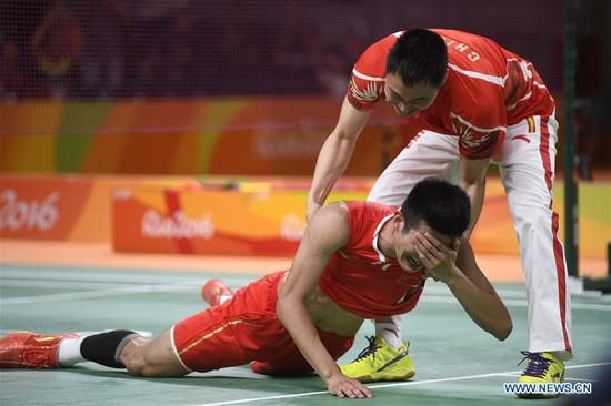 Chen Long (Bottom) of China reacts after beating Lee Chong Wei of Malaysia during the men's singles final of badminton competition at the 2016 Rio Olympic Games in Rio de Janeiro, Brazil, on Aug. 20, 2016. Chen took the title of the event after beating Lee 2-0. (Xinhua/Wang Peng)